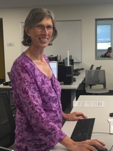 Photograph of Torie Scott at the height-adjustable Research Help Desk